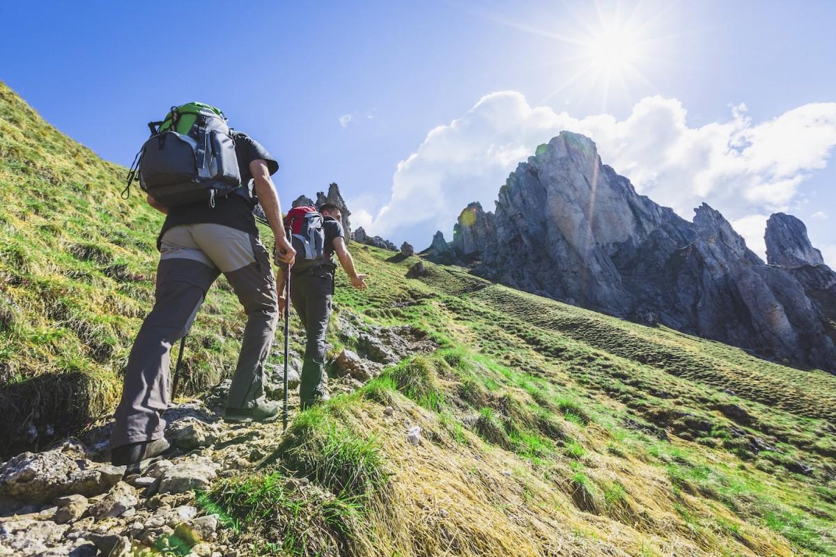 Two people in full walking gear trek along a green hillside, mountains reach into the blue sky in the background