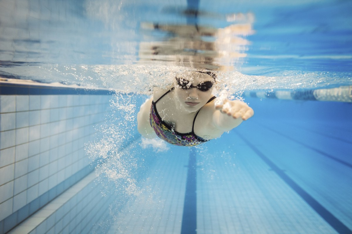 An image of a swimmer in a swimming lane with goggles on and one arm outstretched, taken from underwater