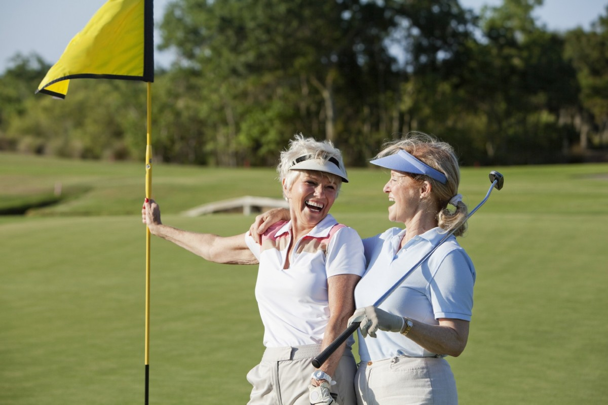 Two women in golf attire, one holding a golf club, stand next to a hole flag smiling and chatting