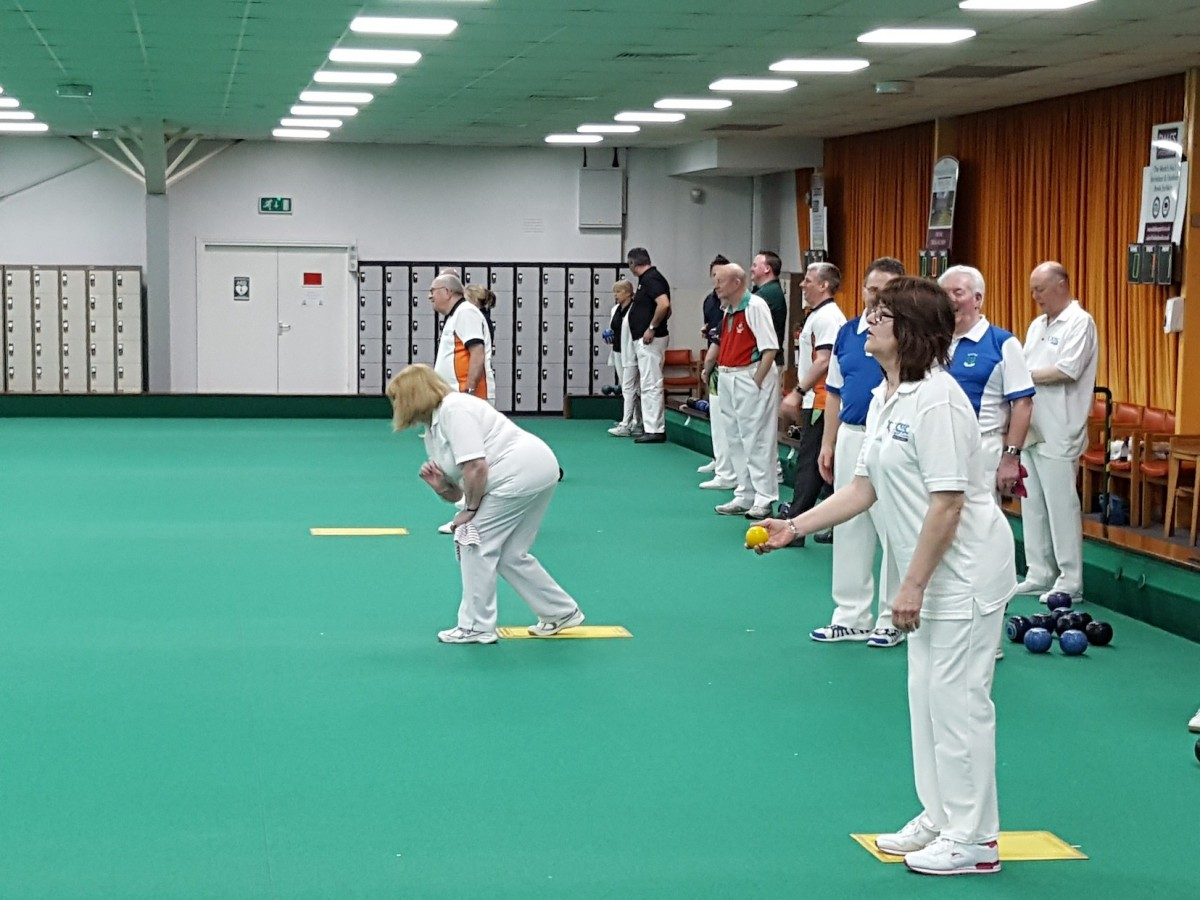 A mixed group of people dressed in white play bowls indoors