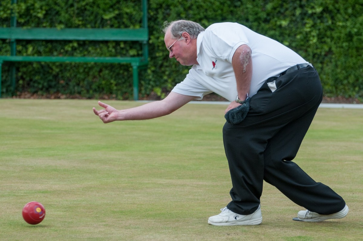 A man playing crown green bowls kneels down, arm extended at the end of the swing