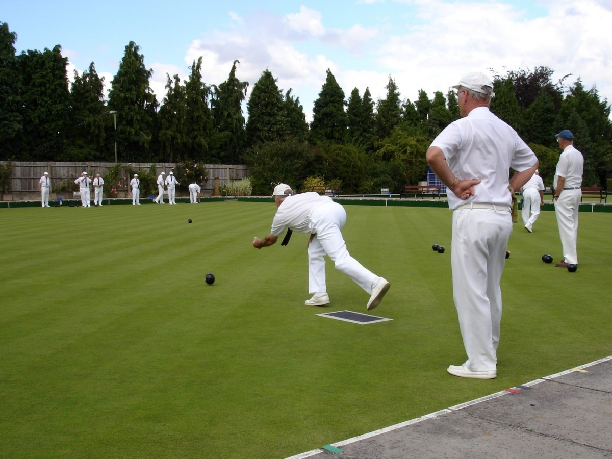 A group of people dressed all in white playing flat green bowls