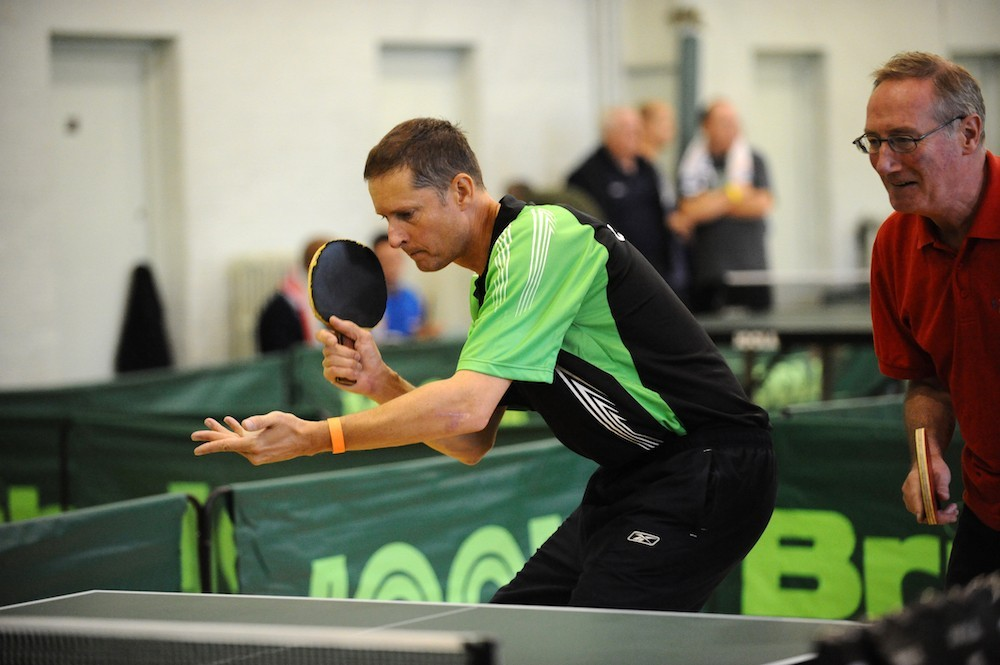 A man holds the bat and ball ready to serve whilst playing table tennis indoors competitively