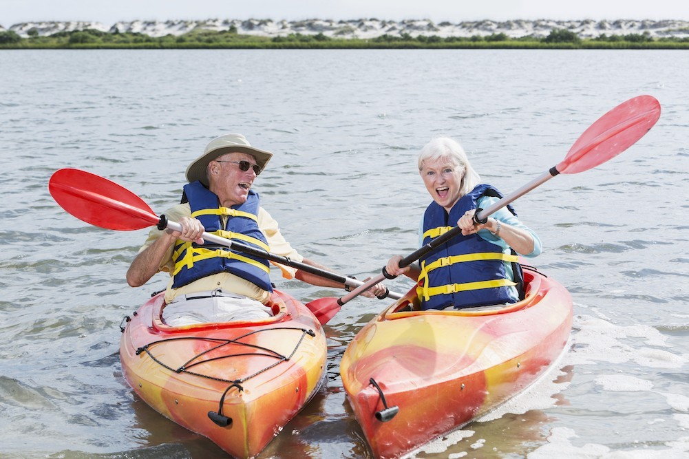 An older couple in life jackets and separate kayaks laugh together whilst kayaking on a lake