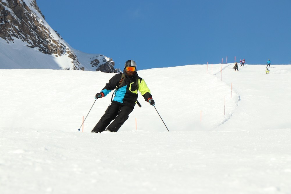 A skier makes their way down a white mountain, a clear blue sky and a little bit of mountain is in the background