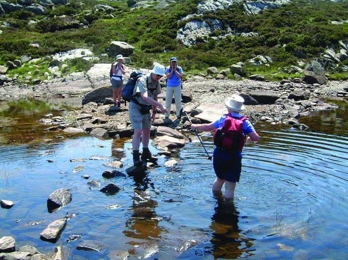 A group of walkers in full walking gear cross a shallow stream