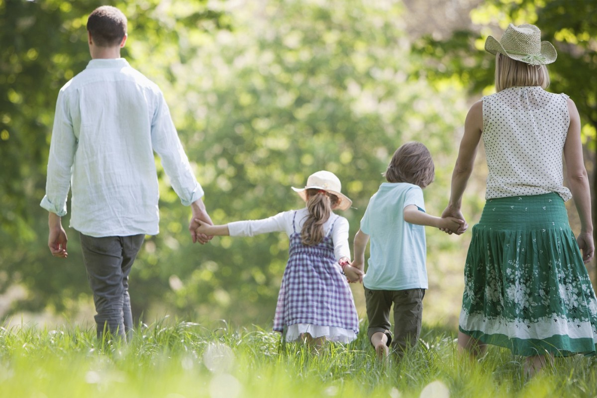 A family of four, two adults and two children, hold hands as they walk through a field