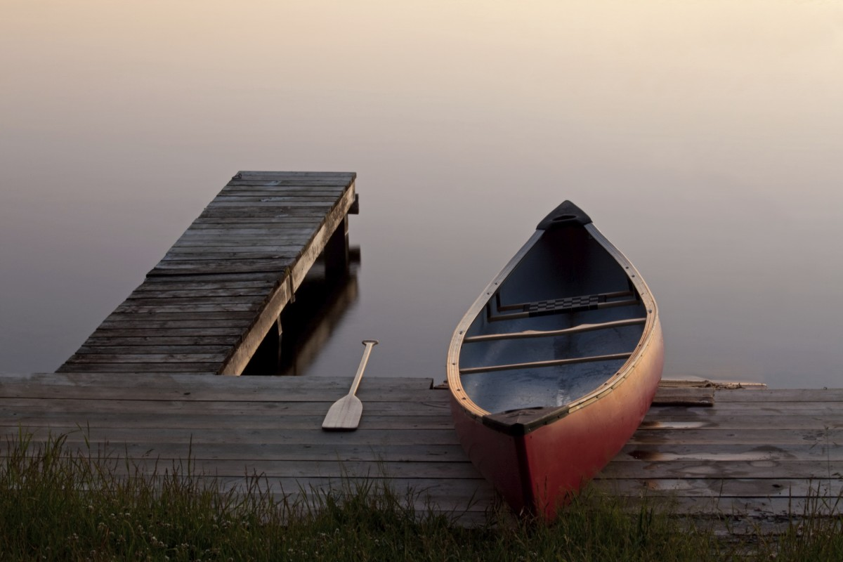 A canoe rests on the shore of a lake with the oar beside it, the sun is setting over the lake