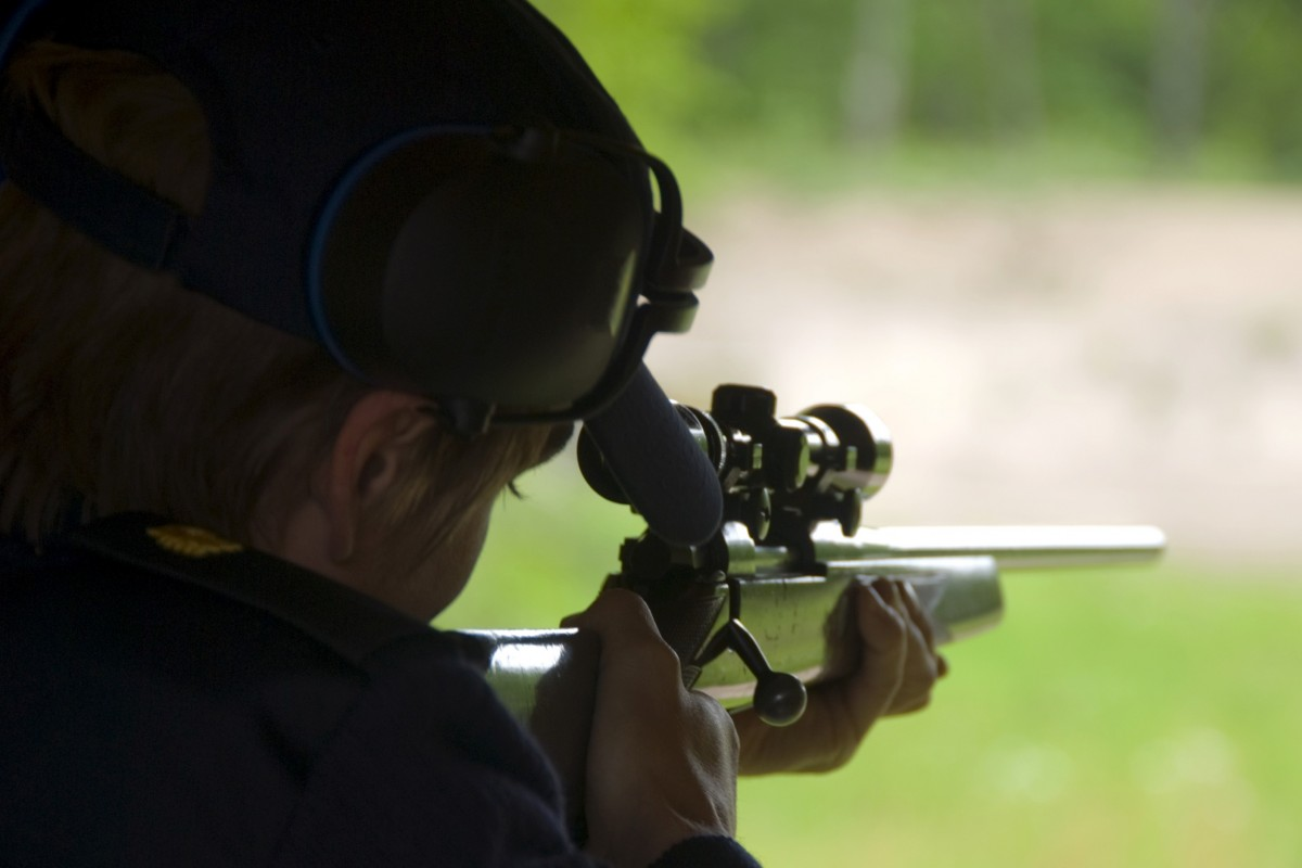A silhouette of a person looking down the sights of a gun, lining up a shot