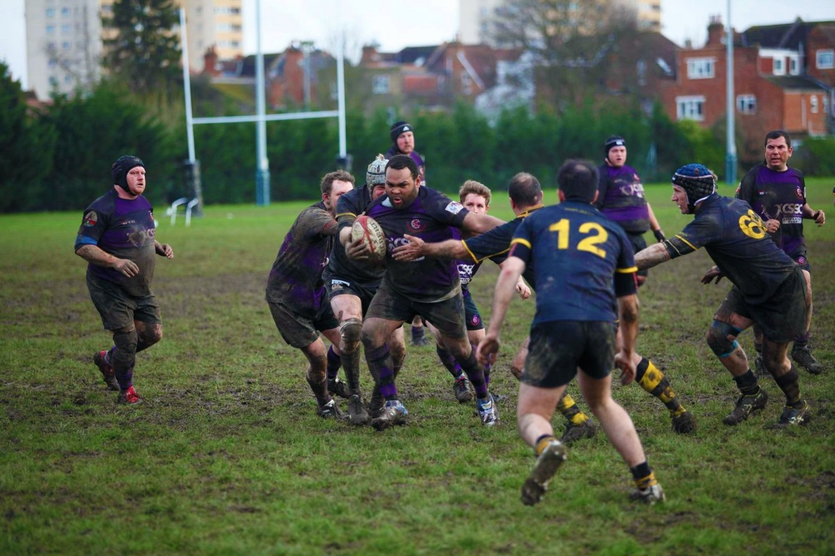 A group of men tackling whilst playing rugby on a muddy field