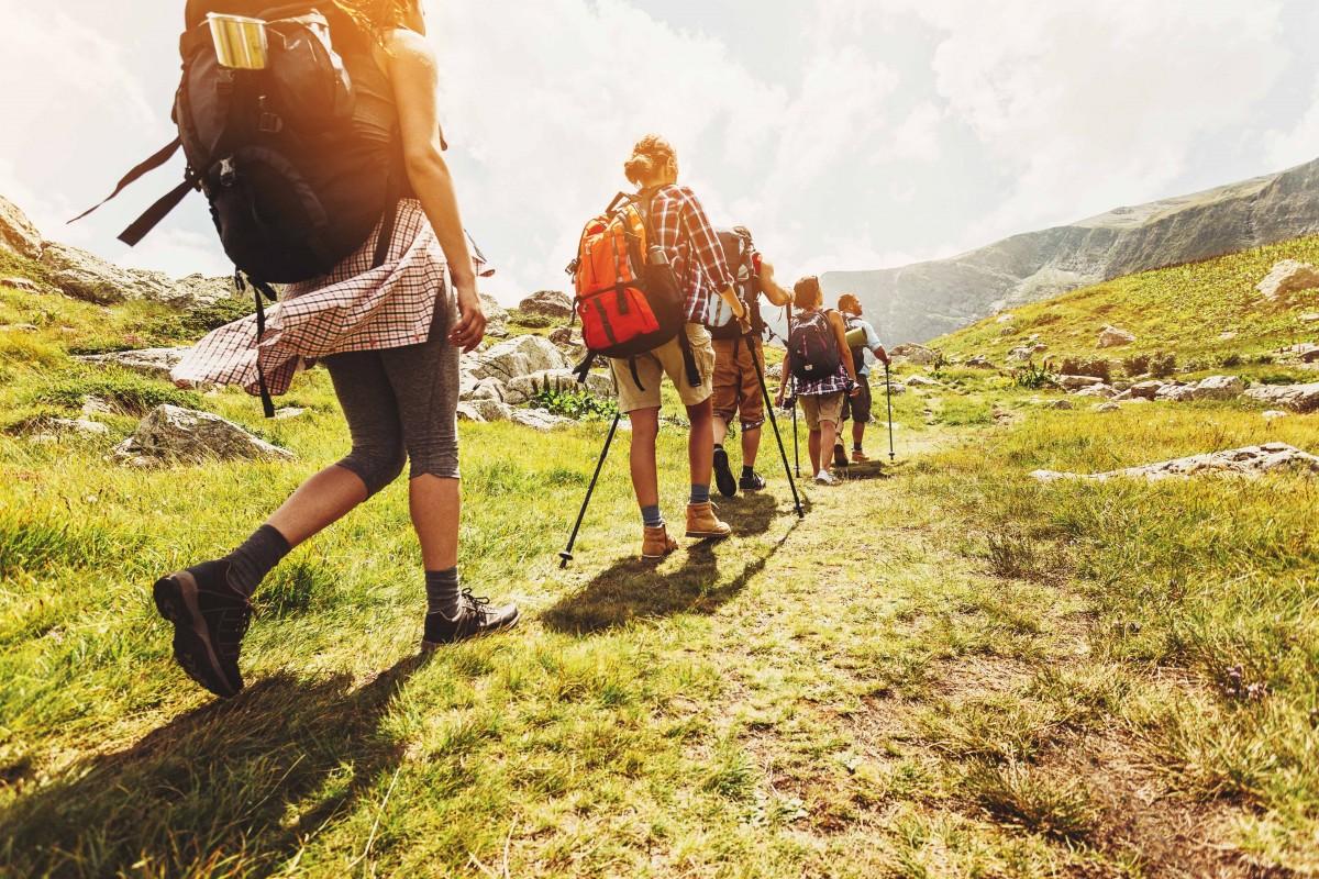 A group of walkers in full gear walk across a grassy hillside