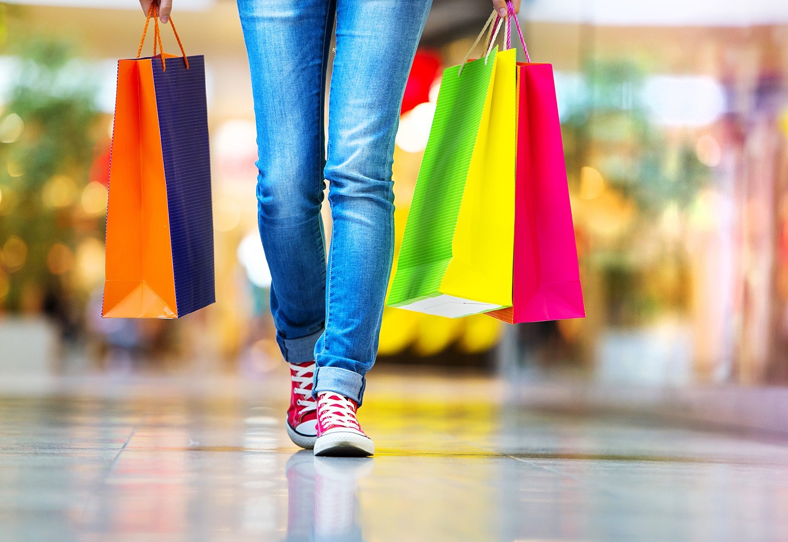 A ground level view of a woman wearing jeans and red converse holding multiple colourful shopping bags
