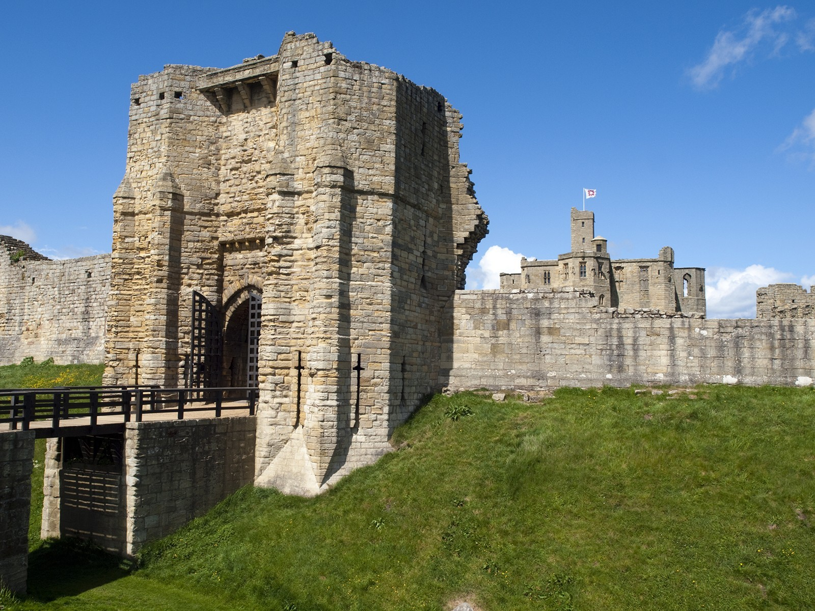 An old castle with a drawbridge on a green hillside with a blue sky