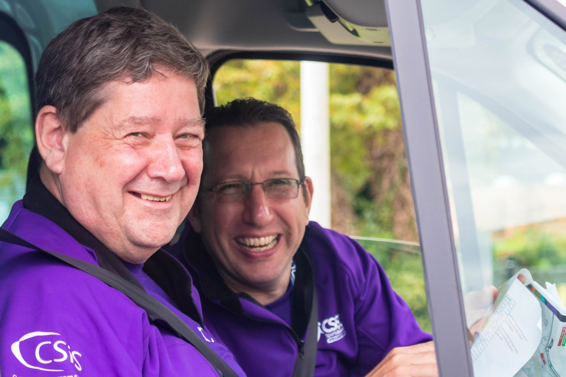 Two CSSC volunteers sat in a minibus smiling at the camera