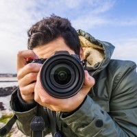 A man wearing a coat looks down the lens of a DSLR camera