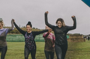 A group of muddy women cheering as they finish a run