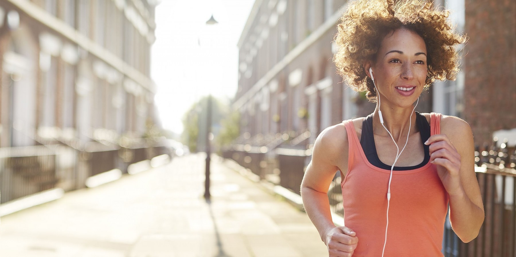 A woman jogging down a residential street listening to headphones