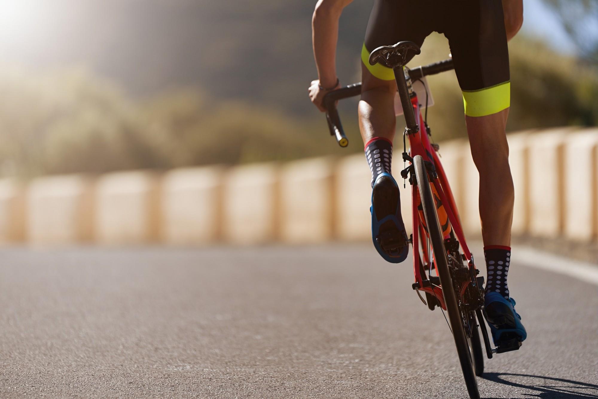 A man sprints on a road bike, riding towards the sun