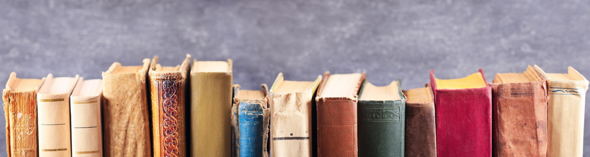 A close up image of old, worn books lined up with their spines facing out