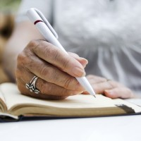 Close-up photo of a person writing in notepad