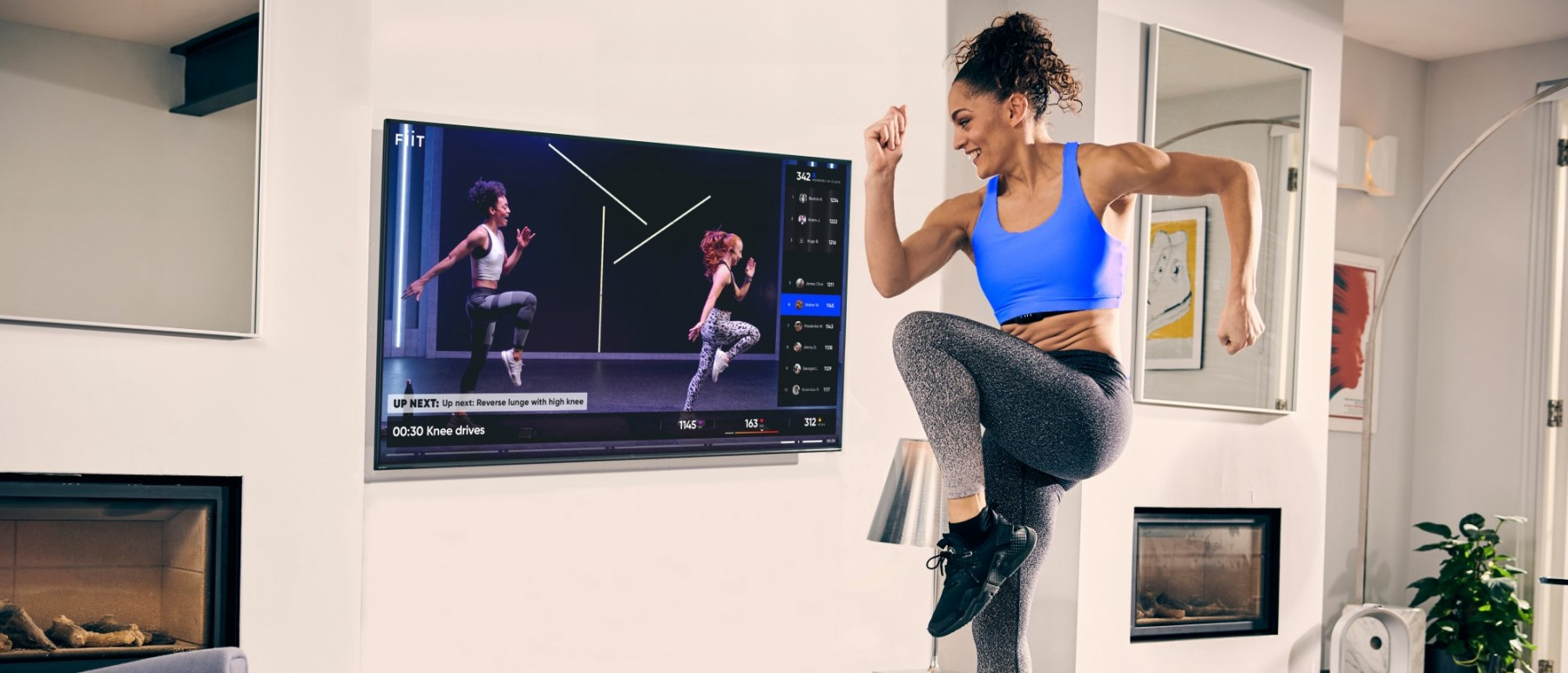 A woman keeping fit at home, watching a fitness video on the TV. She is mid jump, bringing on knee up to her chest