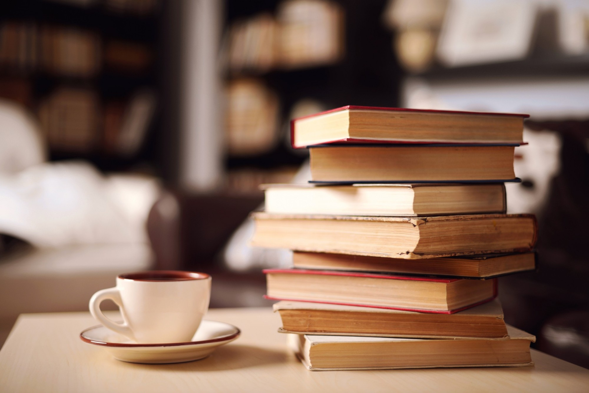 Pile of books next to a teacup on a table