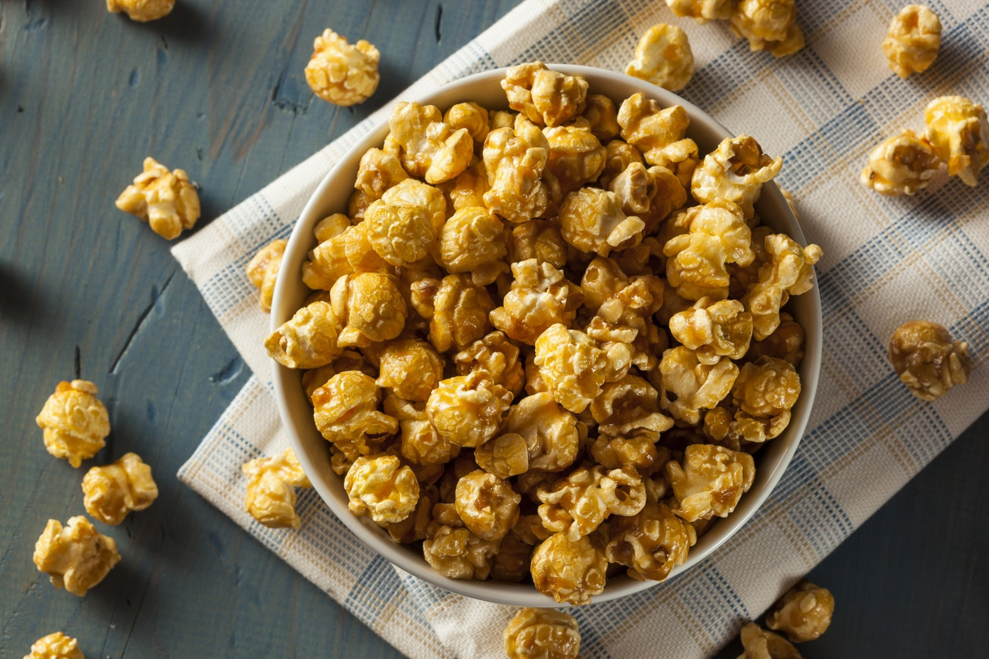 Bowl of popcorn overflowing onto a wooden table