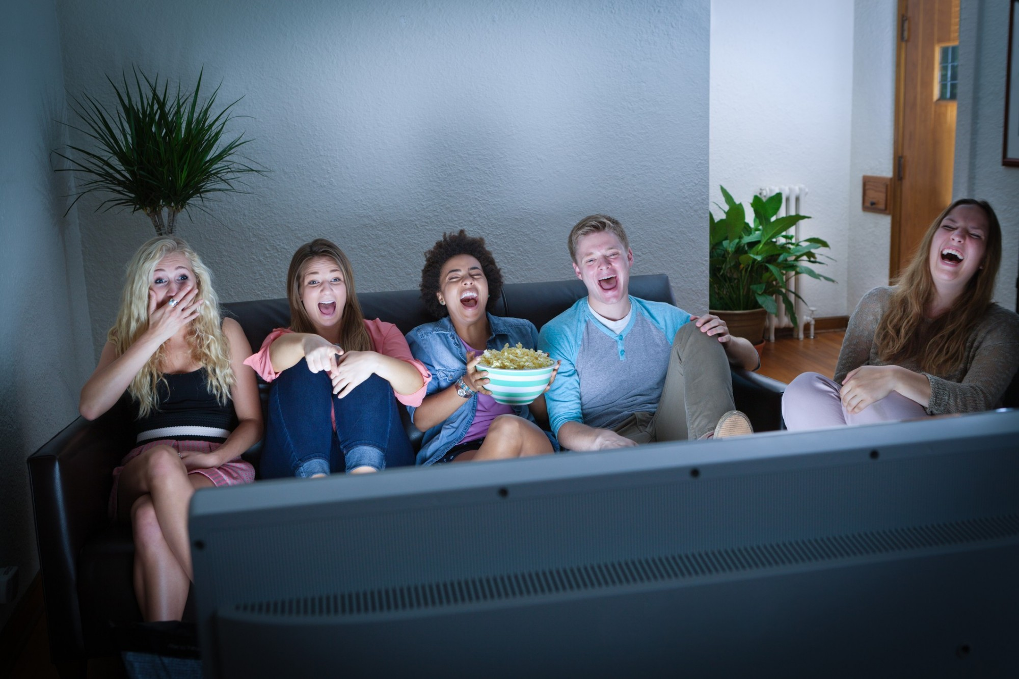 A group of friends sit on the sofa in a low-lit room, eating popcorn and gaping open-mouthed watching a film