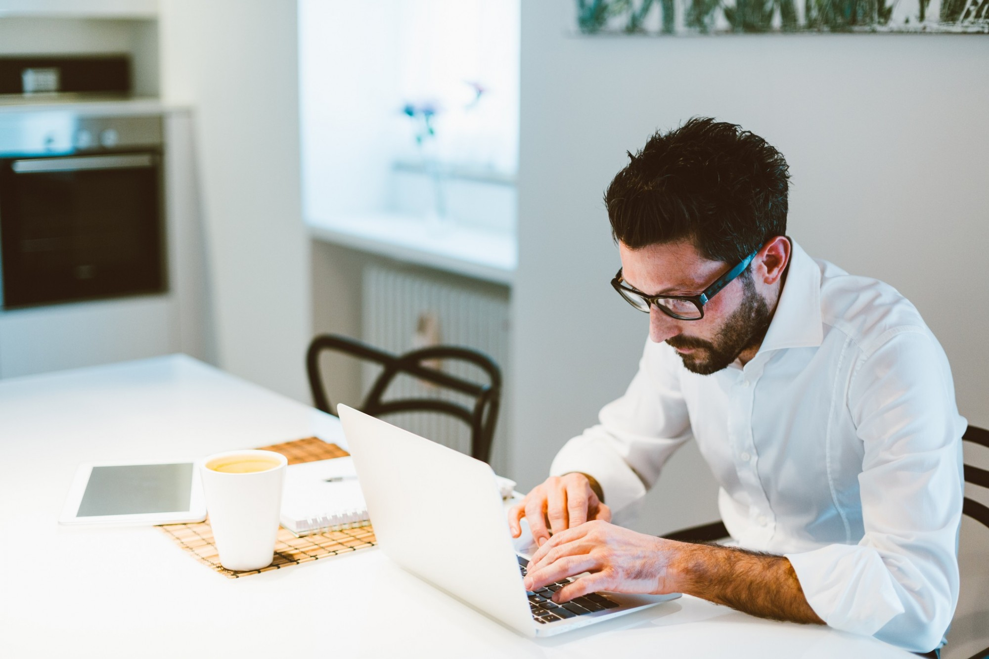 Man sitting at a table with a laptop and cup of coffee