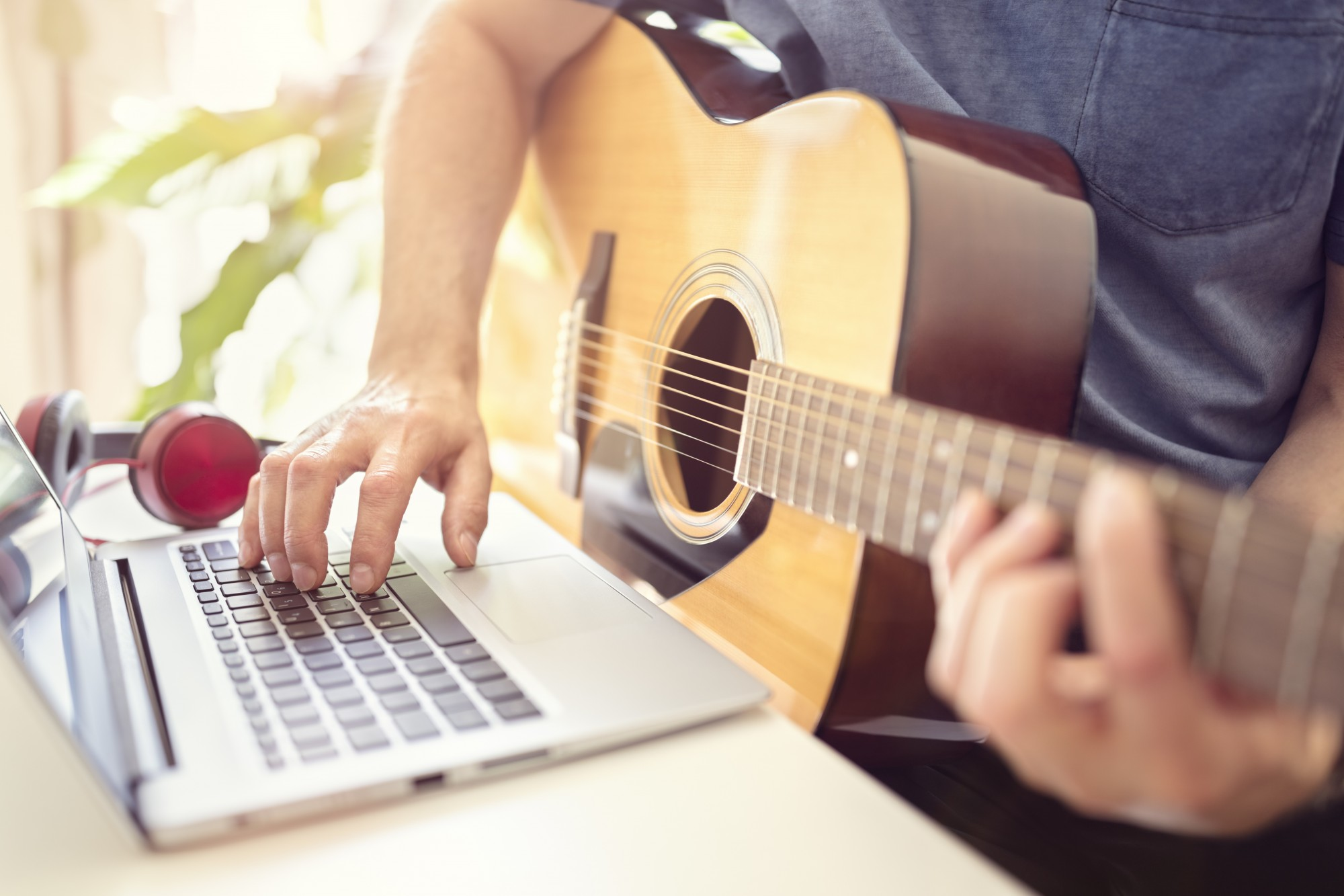 Person sat at a desk playing an acoustic guitar