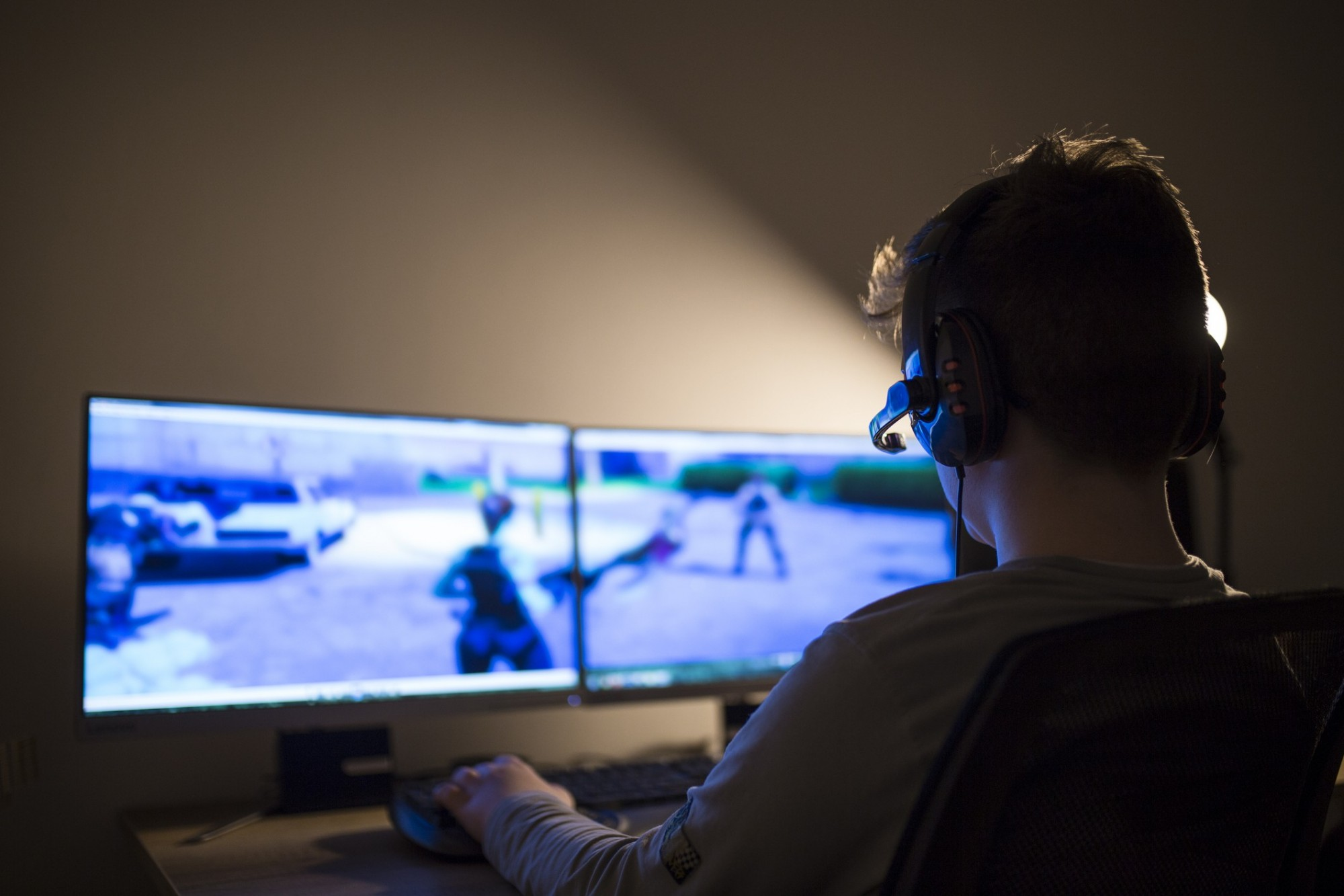 Gamer sat in front of a dual screen moniter playing a 3rd person game