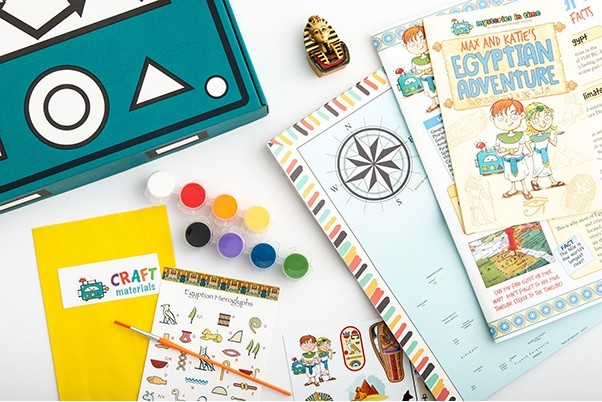 A collection of things in the mysteries in time box, including a small set of paints, stickers, worksheets and a map