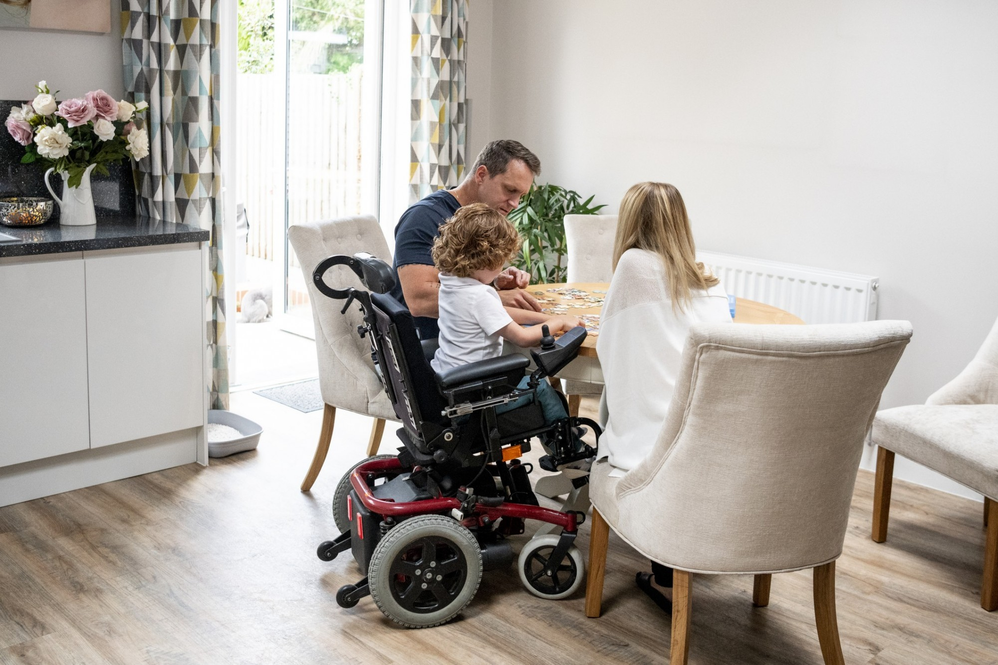 A family sit around the table in their kitchen playing a game together, the little boy is in a motorised wheelchair