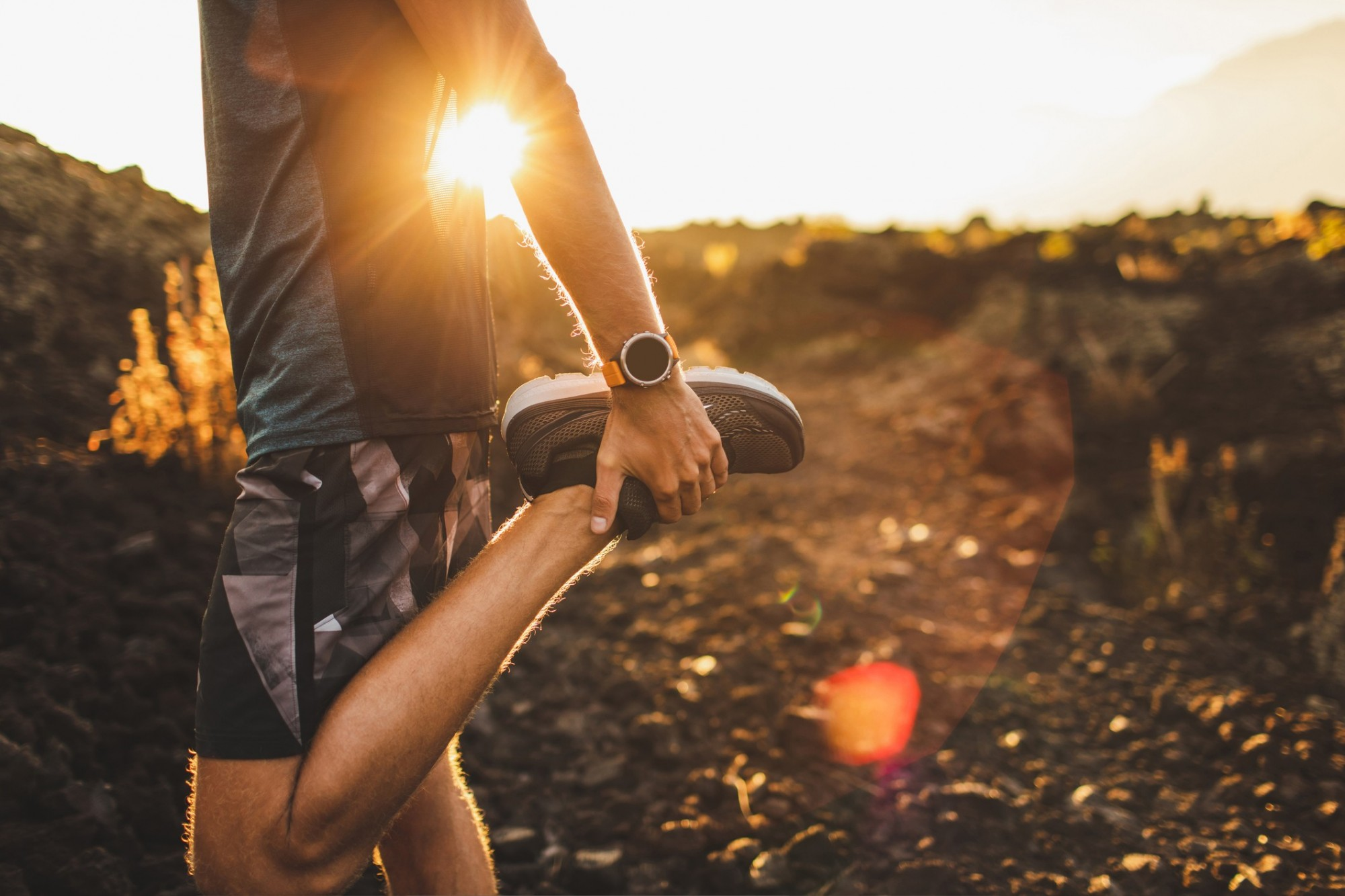 A runner pulls their foot up to stretch their quadricep, the sun is setting in the background