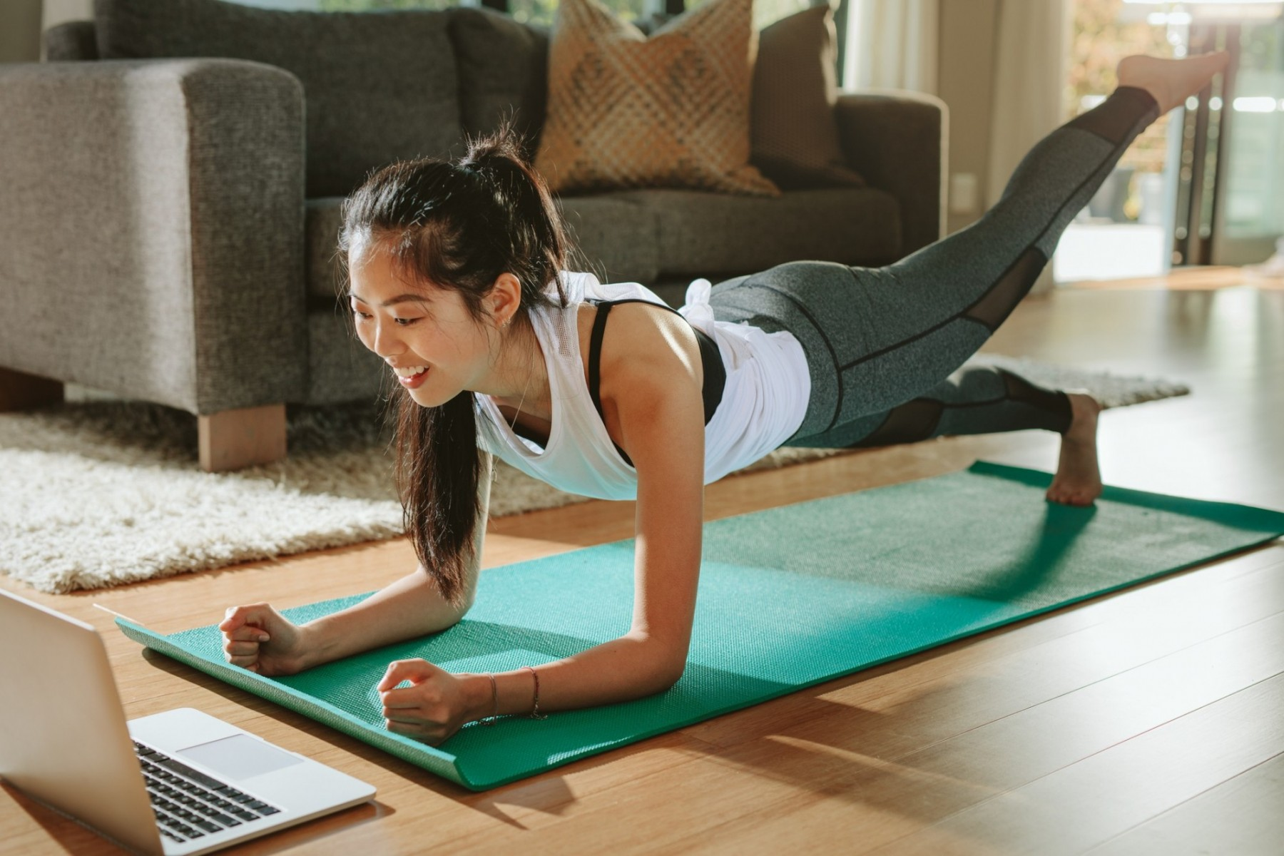 A woman doing a plank on a yoga mat at home with one leg raised in the air