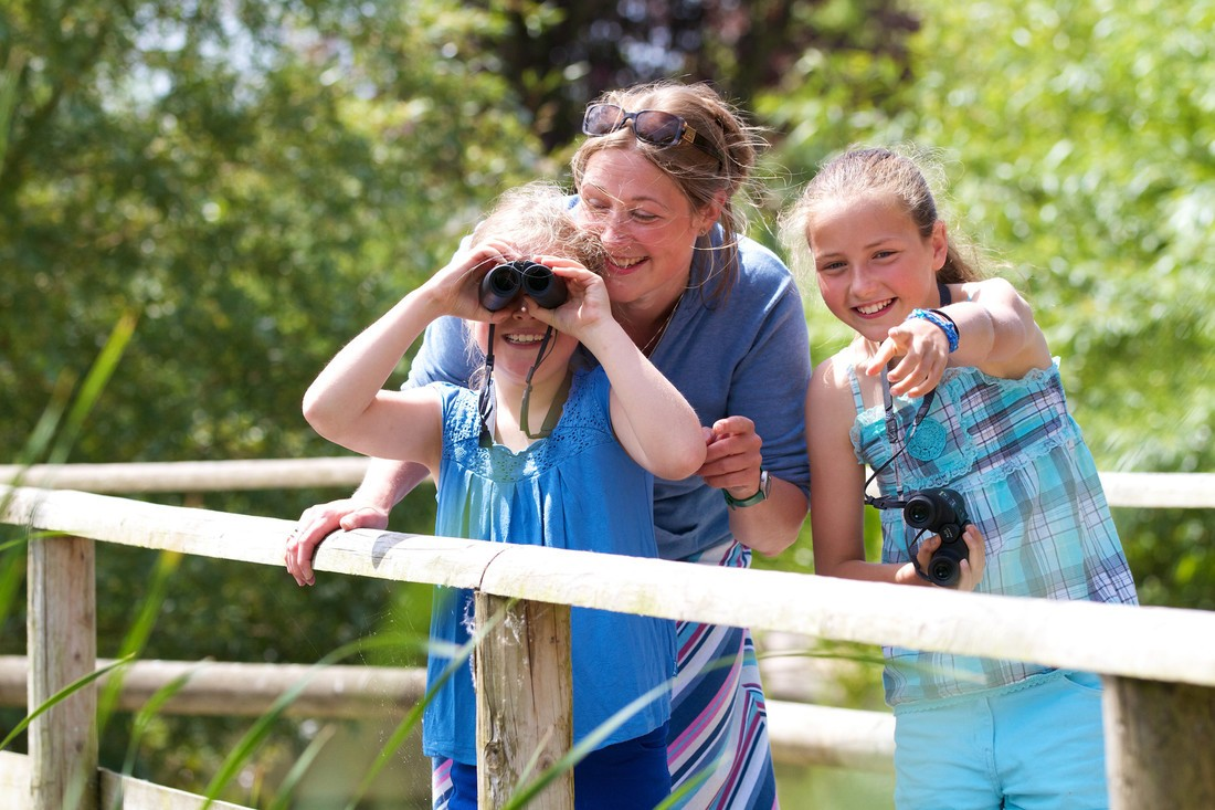 A mother and two little girls stand on a bridge, one girl is looking at birds through binoculars and the other girl is pointing into the camera