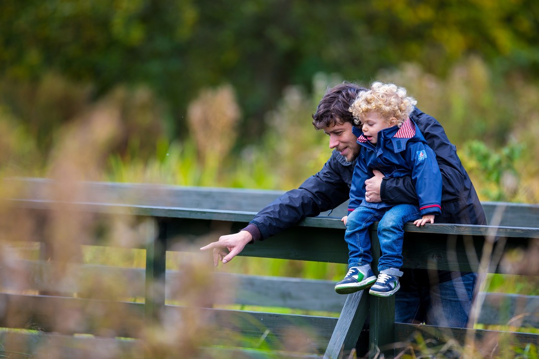 A father holds a toddler as he sits on the top of a bridge railing, the father is pointing down out of shot