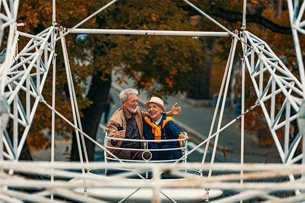 An older couple look at one another and laugh as they ride a ferris wheel in autumn