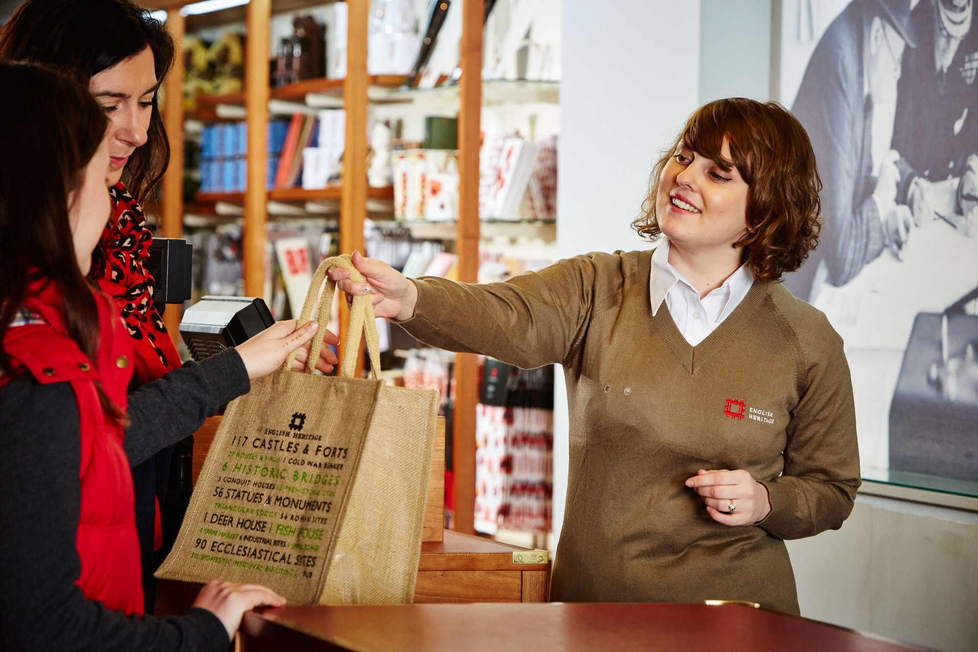A woman serving someone at an english heritage shop
