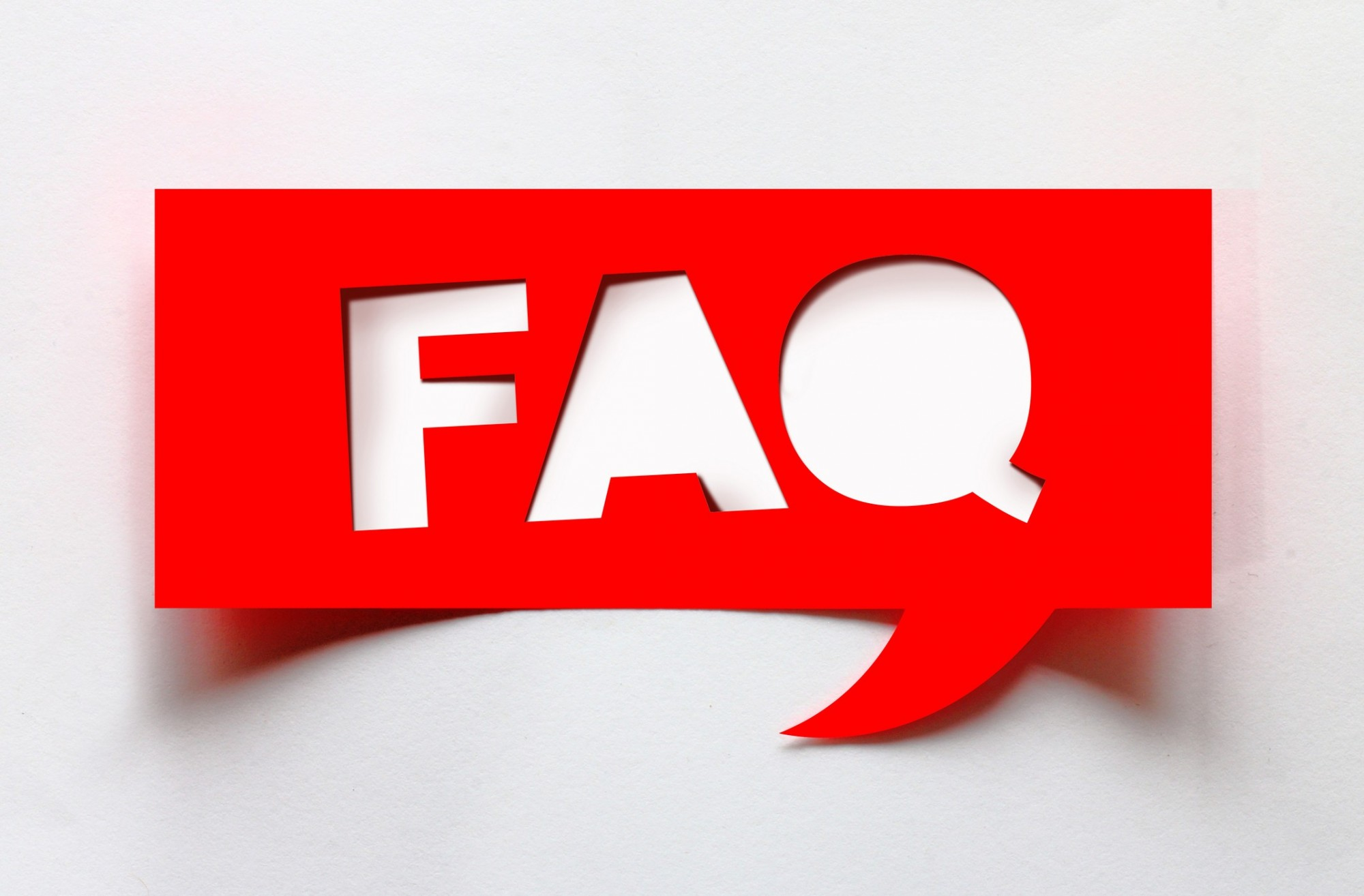 The letters F A Q have been cut out of a red piece of card which is in the shape of a speech bubble