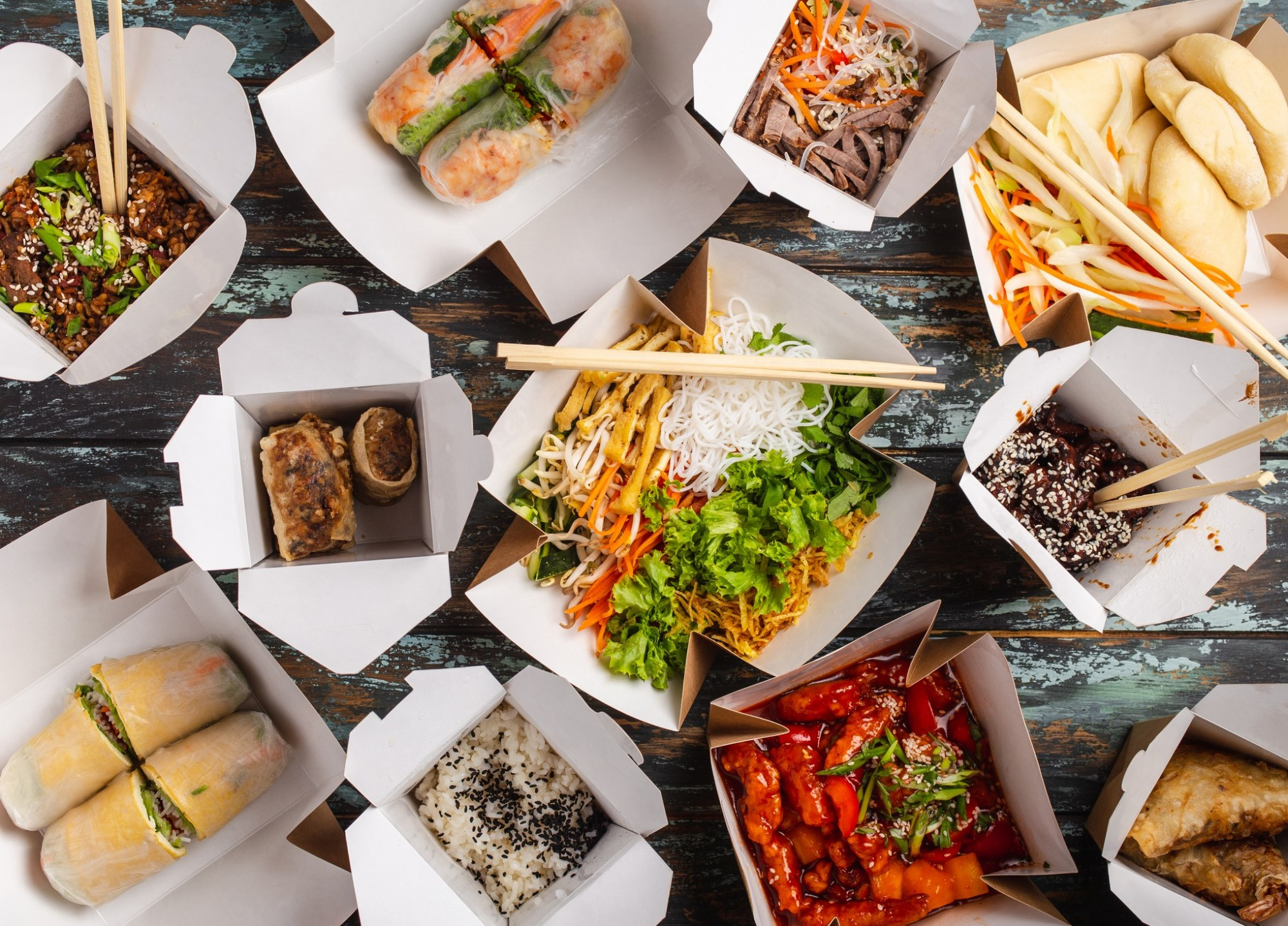 Spread of Asian food in boxes on a wooden table with chopsticks