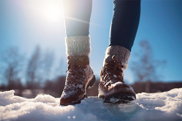 A close up of someone's feet and calves, wearing hiking boots and walking in snow