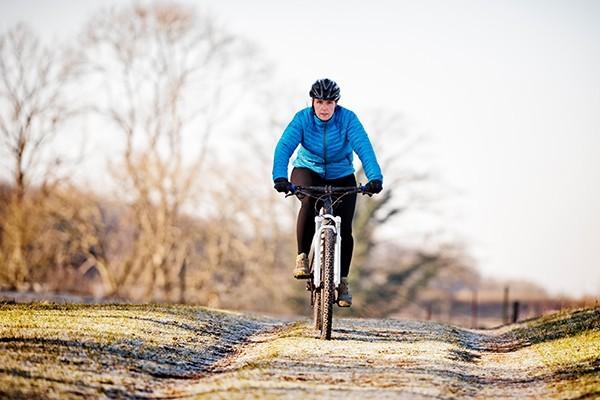 A woman riding a bike across a frosty path