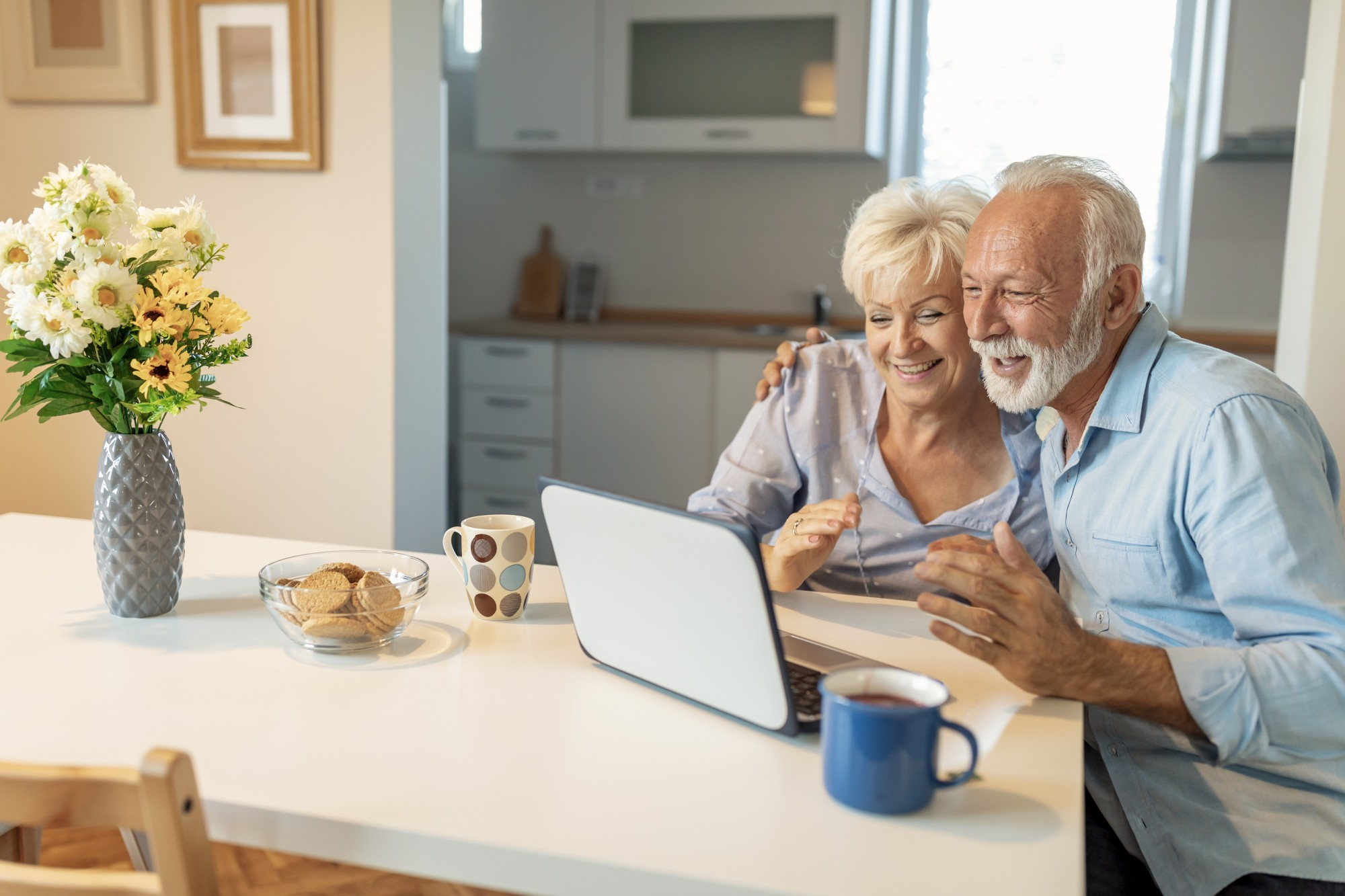A senior couple cudding up in front of a laptop drinking coffee