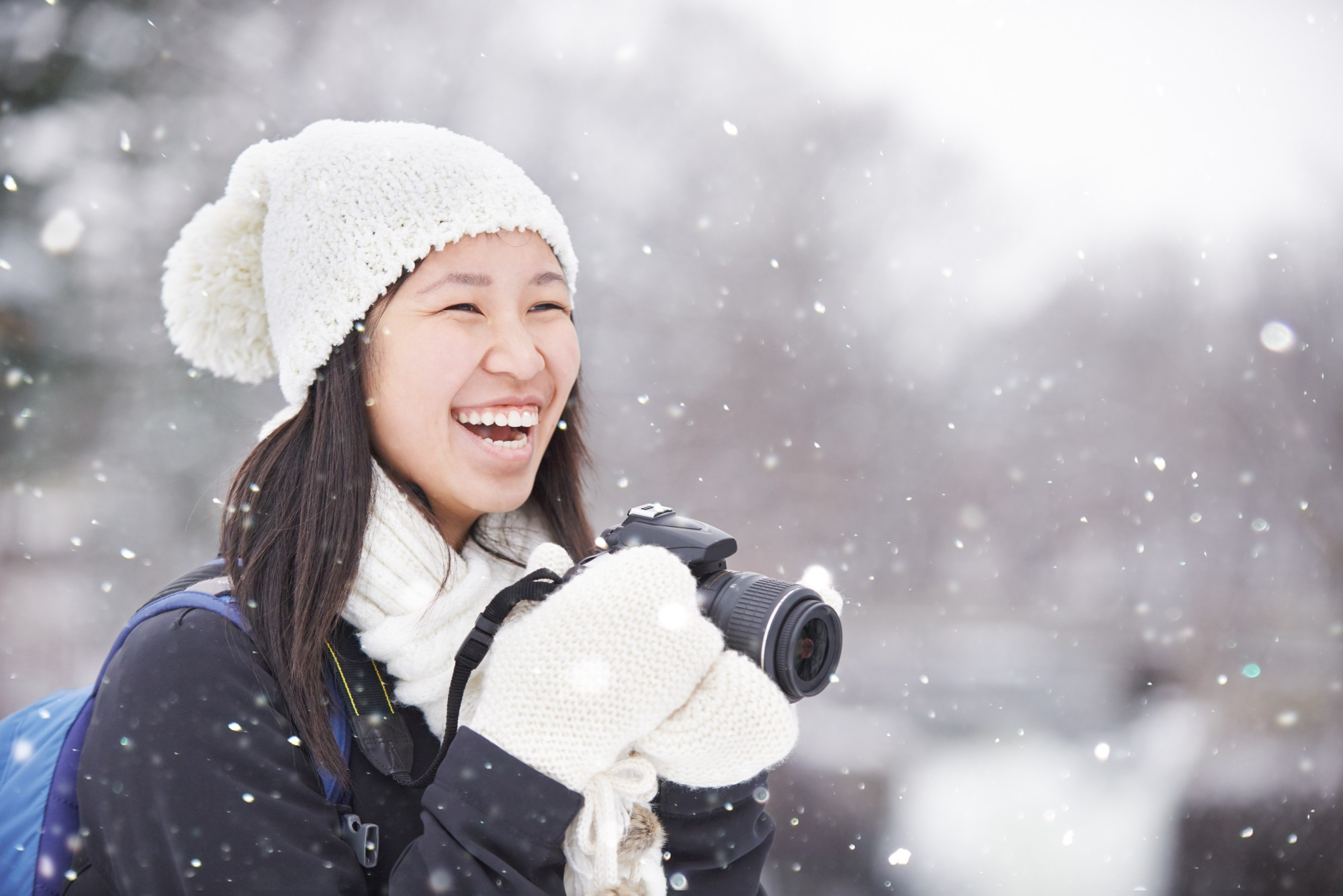A woman wearing a hat an mittens laughs whilst holding a camera