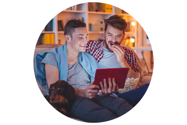 A gay couple sit on the sofa watching a movie on a tablet eating popcorn