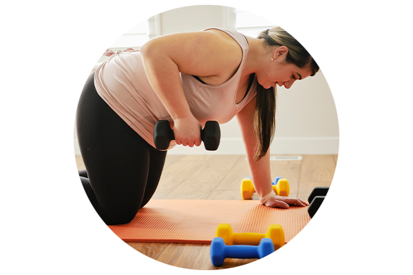 A woman working out from home with dumbbells