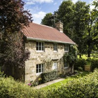 An English Heritage holiday cottage, stone cottage nestled in trees and hedgerow