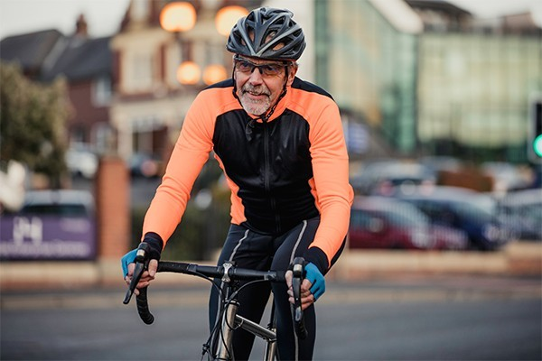 A lady with grey hair grins as she rides a bike down an avenue
