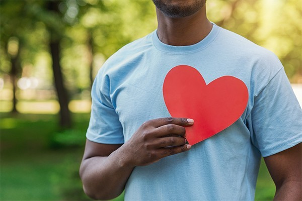 a man holding a red heart over his chest